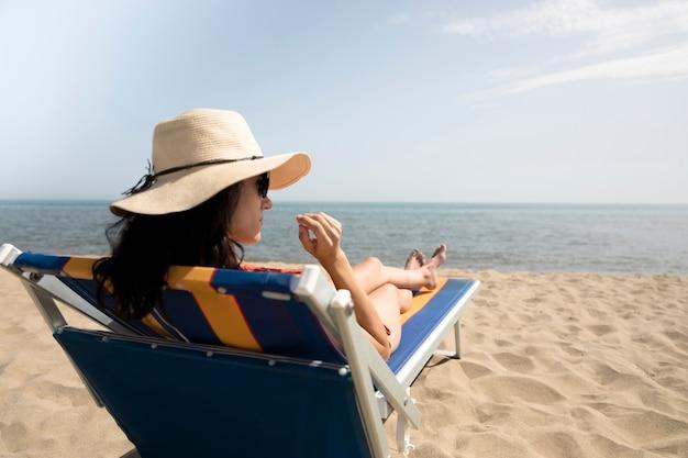 Chiuda sulla donna posteriore di vista sulla sedia di spiaggia che osserva via