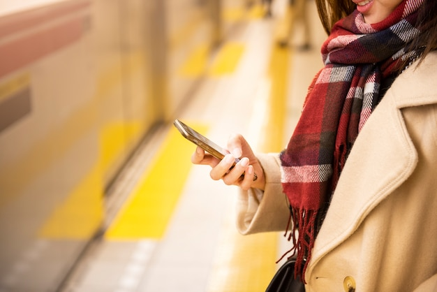 Chiuda sulla donna sta giocando lo smart phone