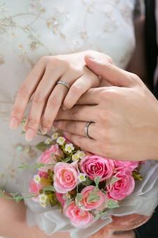 Chiuda sulla fede nuziale degli articoli della mano dello sposo e della sposa