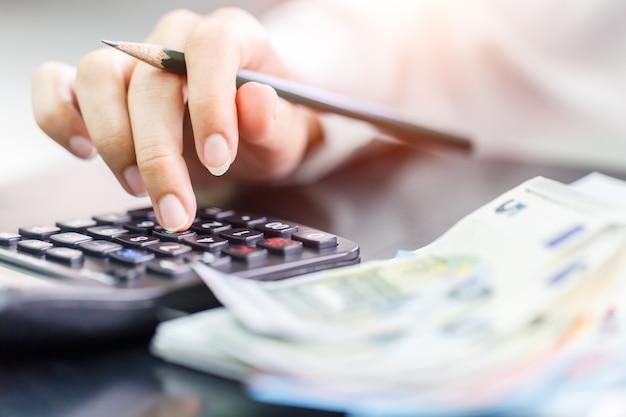 Chiuda sulla femmina della mano destra facendo uso del calcolatore e della tenuta della mano sinistra con le euro banconote.