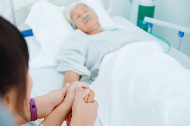 Chiuda sulla figlia e sulla nipote che tengono le mani anziane della donna nella stanza di ospedale.