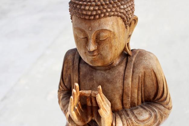 Chiuda sulla figura di legno del buddha