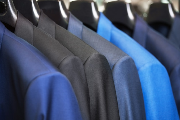 Chiuda sulla fila del vestito di signori di stile lussuoso, appeso in un armadio.