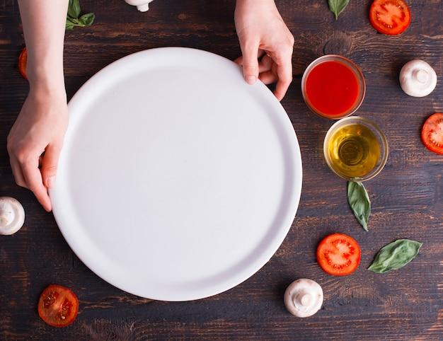 Chiuda sulla foto del piatto pulito bianco sulla tavola di legno scura