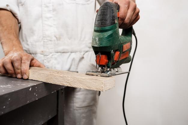 Chiuda sulla foto del taglio del legno con la sega a catena.