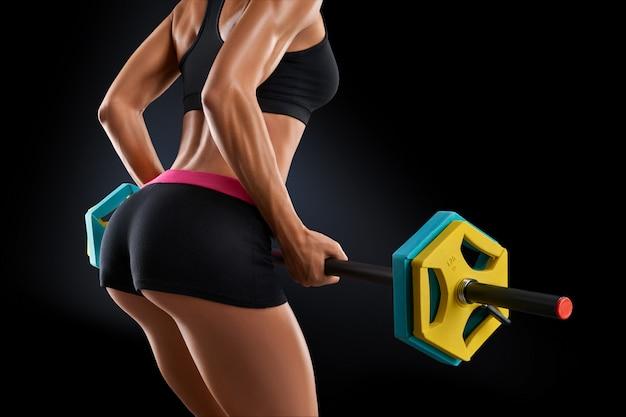 Chiuda sulla foto dell'allenamento della donna di forma fisica con il bilanciere alla palestra
