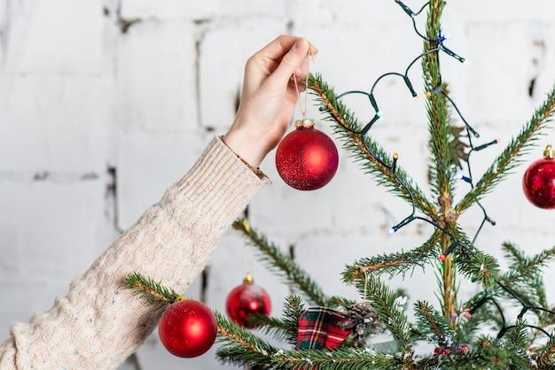 Chiuda sulla foto della mano che appende le palle rosse sull'albero di natale