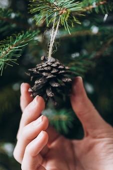 Chiuda sulla foto della mano che tiene le palle rosse sull'albero di natale
