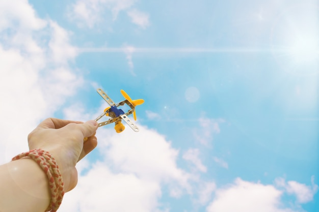 Chiuda sulla foto della mano dell'uomo che tiene aeroplano giocattolo contro il cielo blu