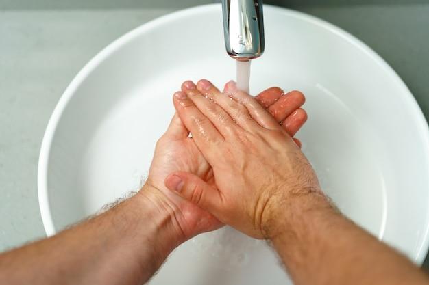 Chiuda sulla foto delle mani maschii che lavano con il sapone sopra il lavandino