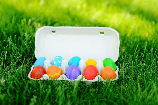 Chiuda sulla foto delle uova di pasqua variopinte su un'erba verde all'aperto