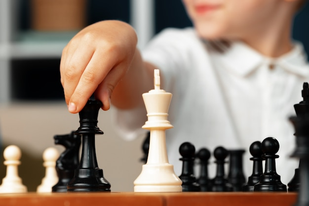 Chiuda sulla foto di un ragazzino che gioca gli scacchi