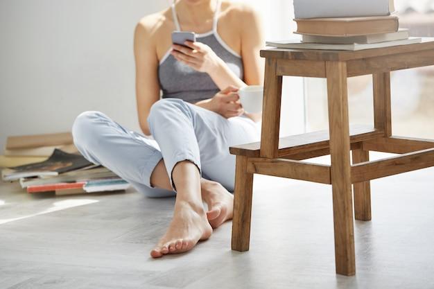 Chiuda sulla foto di web praticante il surfing della giovane donna adolescente al telefono che tiene la tazza che si siede sul pavimento fra i vecchi libri vicino alla finestra sopra la parete bianca.