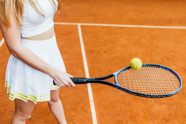 Chiuda sulla foto, ragazza che gioca a tennis sulla corte.