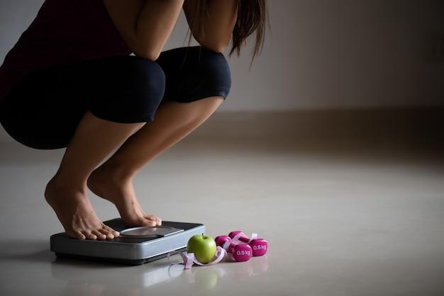 Chiuda sulla gamba femminile turbata che fa un passo sulle bilance con nastro adesivo di misurazione.