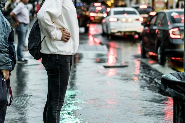 Chiuda sulla gente che cammina nella via della città durante la pioggia persistente