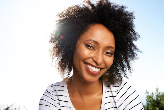 Chiuda sulla giovane donna africana attraente che sorride all'aperto contro il sole luminoso
