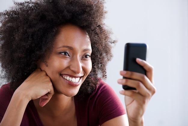 Chiuda sulla giovane donna africana felice che per mezzo dello smart phone