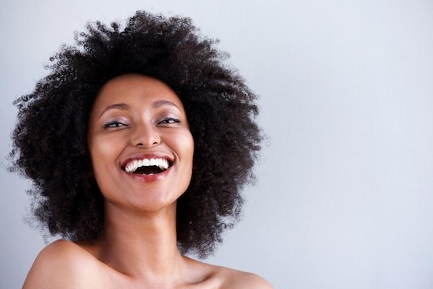 Chiuda sulla giovane donna attraente con le spalle nude che ridono del fondo grigio