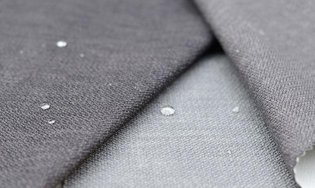 Chiuda sulla goccia di acqua sul tessuto grigio dell'iuta. concetto per superfici facili da pulire e impermeabili