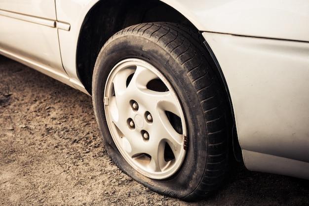 Chiuda sulla gomma piana e sulla vecchia automobile sulla riparazione aspettante della strada