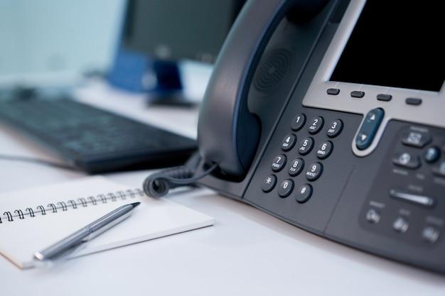 Chiuda sulla linea terrestre del telefono al concetto dell'ufficio