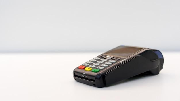 Chiuda sulla macchina di pagamento per il pagamento della fattura vicino alla tavola