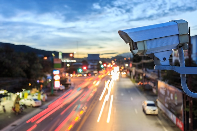Chiuda sulla macchina fotografica del cctv di sicurezza che funziona sopra la strada