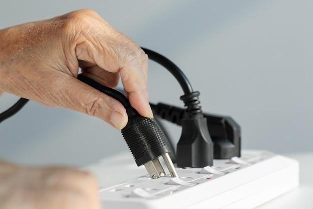 Chiuda sulla mano anziana che si collega alla presa elettrica
