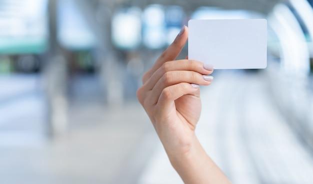 Chiuda sulla mano caucasica della donna che tiene il biglietto da visita bianco in bianco sul fondo vago del percorso del corridoio per, mostri, promuova il contenuto e il messaggio