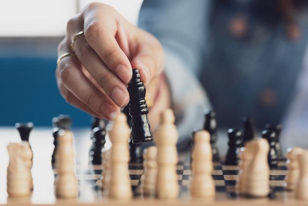Chiuda sulla mano che gioca il gioco di scacchi