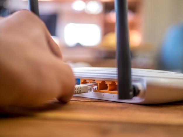 Chiuda sulla mano che inserisce il cavo di ethernet in router di wi-fi sulla tavola di legno