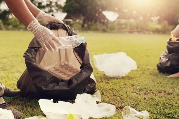 Chiuda sulla mano che prende la plastica dell'immondizia per la pulizia al parco