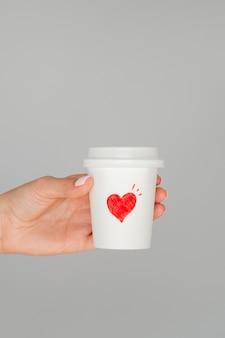 Chiuda sulla mano che tiene il caffè del biglietto di s. valentino
