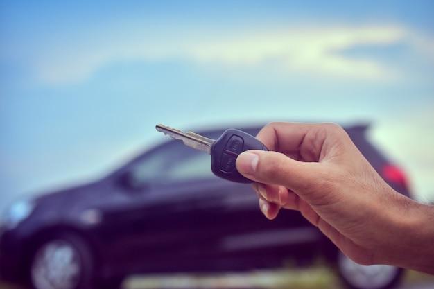 Chiuda sulla mano che tiene l'automobile chiave