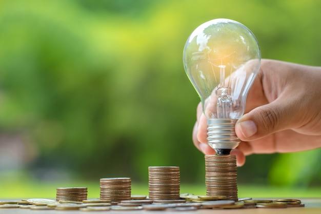 Chiuda sulla mano che tiene la lampadina con la pila delle monete sulla tavola di legno.