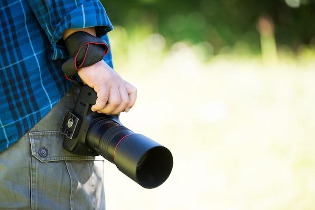 Chiuda sulla mano che tiene la macchina fotografica professionale del dslr