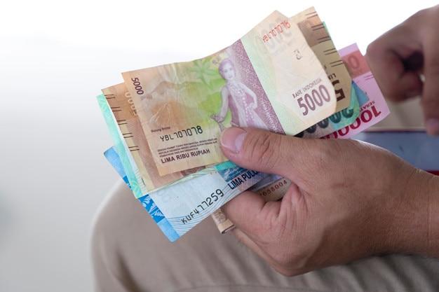 Chiuda sulla mano che tiene le banconote della rupia, valuta dell'indonesia