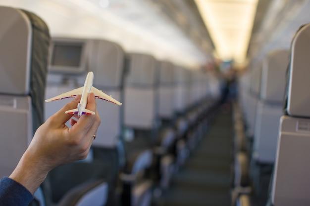 Chiuda sulla mano che tiene un modello dell'aeroplano dentro un grande aereo