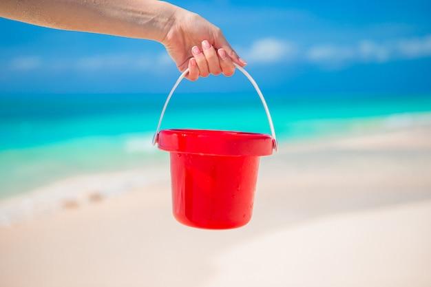 Chiuda sulla mano che tiene un piccolo secchio rosso sulla spiaggia tropicale