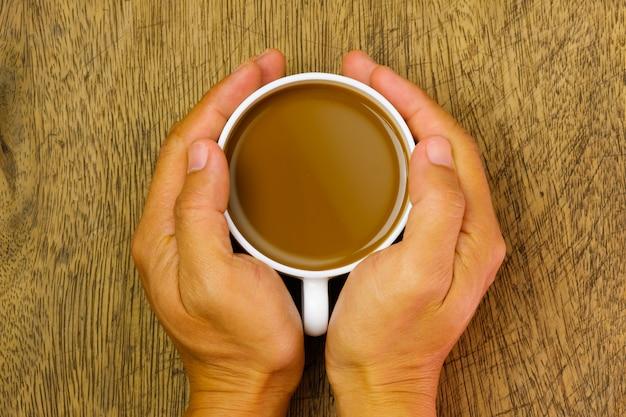 Chiuda sulla mano che tiene una tazza di cacao sopra la tavola di legno, vista superiore