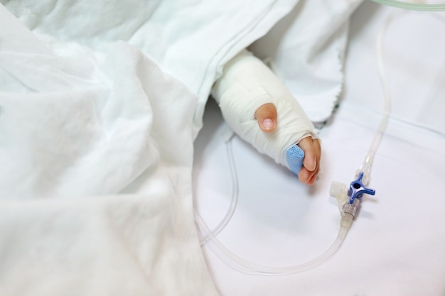 Chiuda sulla mano del bambino sul letto del paziente in ospedale con endovenoso salino.