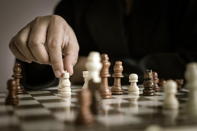 Chiuda sulla mano del colpo della donna di affari che gioca la profondità di campo bassa selezionata del fuoco della scacchiera