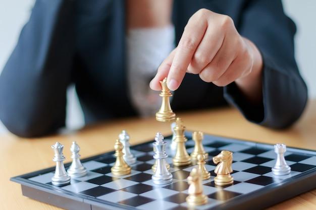 Chiuda sulla mano del colpo della donna di affari che sposta scacchi dorati