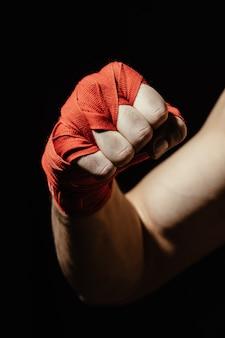 Chiuda sulla mano del pugile in fasciatura rossa
