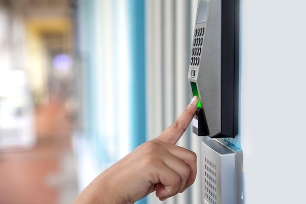 Chiuda sulla mano del sistema di sicurezza digitale elettronico della serratura di porta dell'impronta digitale di esame asiatico della donna
