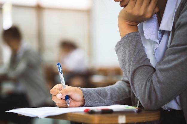 Chiuda sulla mano dell'esame di lettura e di scrittura dello studente con lo sforzo in aula