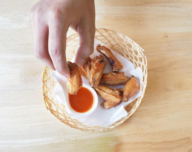 Chiuda sulla mano dell'essere umano raccogliere il pollo fritto e immergerlo in salsa.