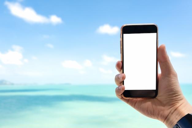 Chiuda sulla mano dell'uomo che tiene smartphone nero sul bello mare blu calmo e sul fondo bianco del cielo.