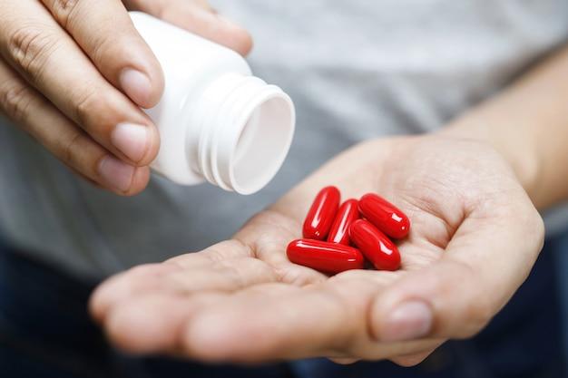 Chiuda sulla mano dell'uomo che tiene una medicina, con versa la vitamina delle pillole dalla bottiglia.